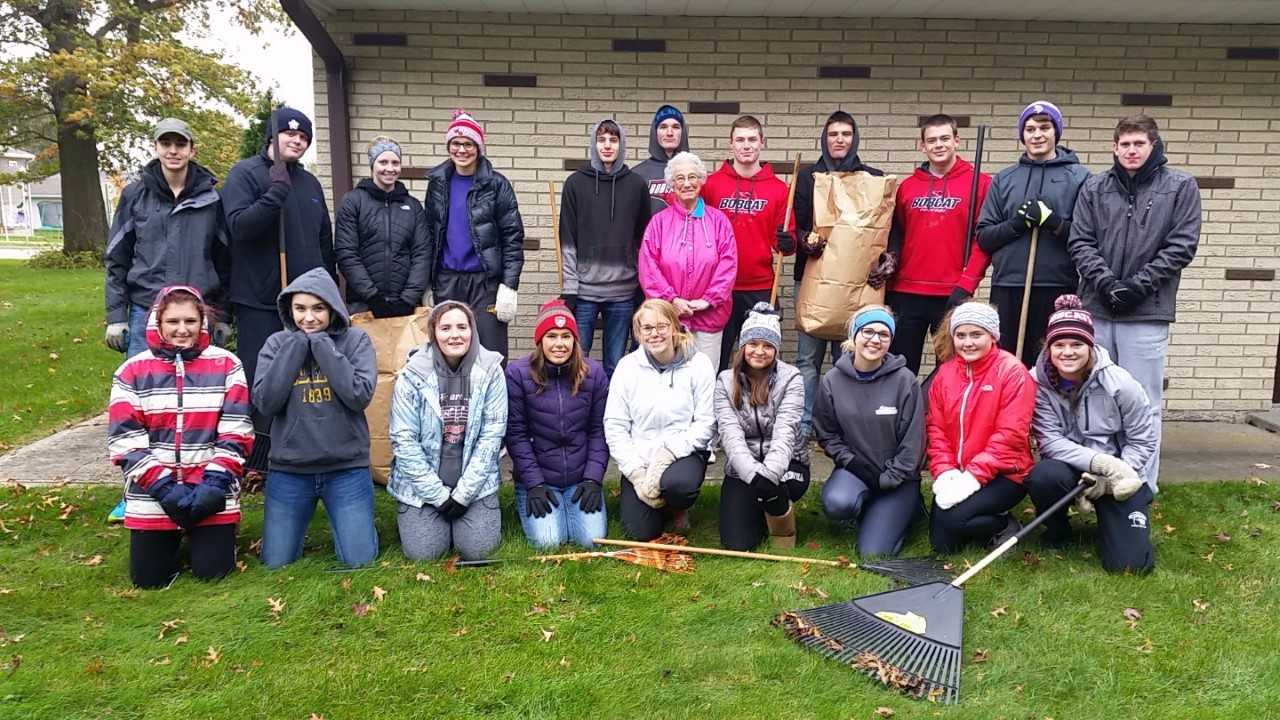 Students raking leaves for Bobcat Pride Day