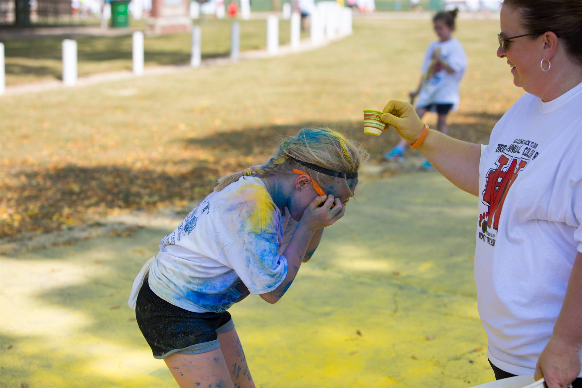 girl getting yellow color at color run