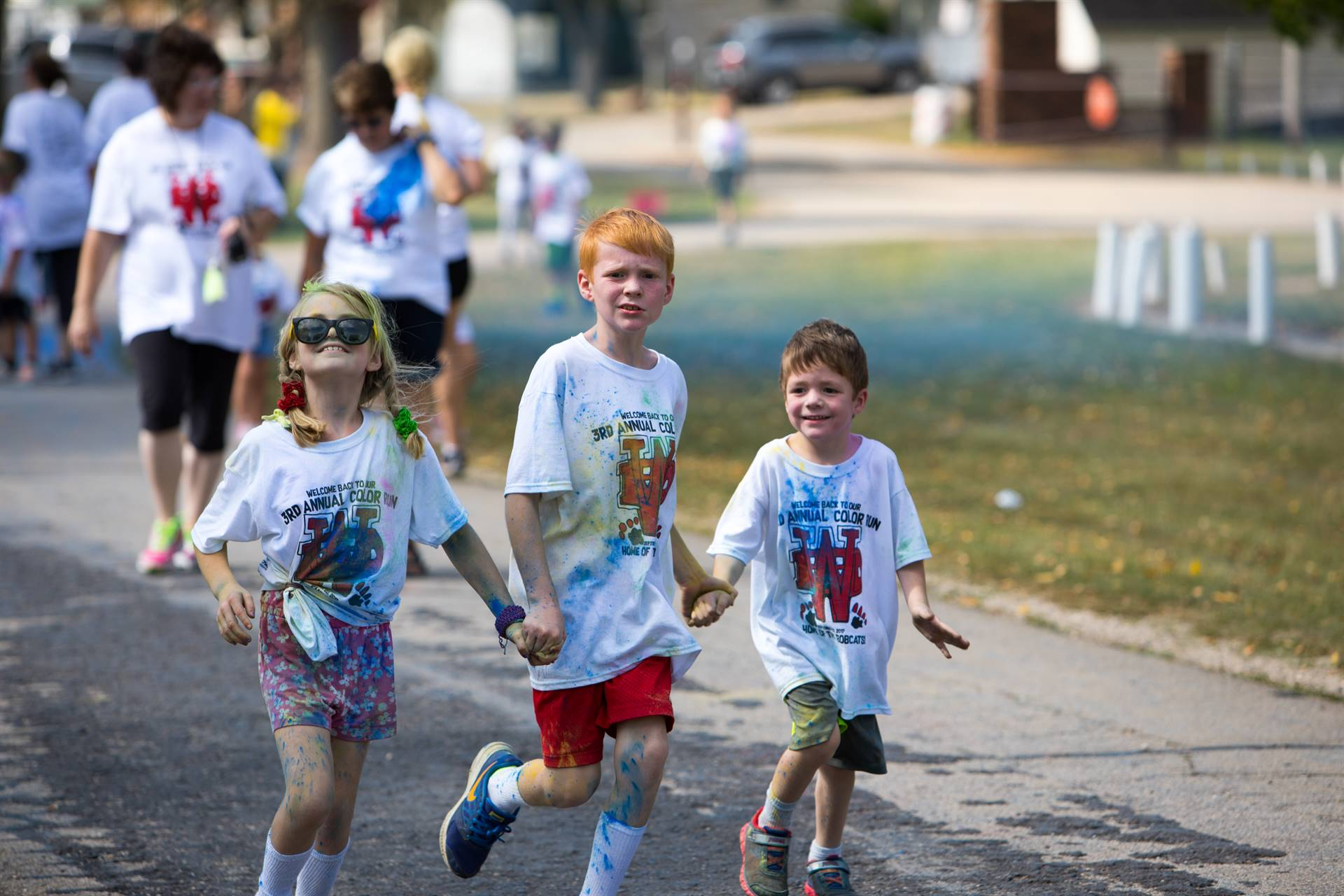 3 kids holding hands at color run