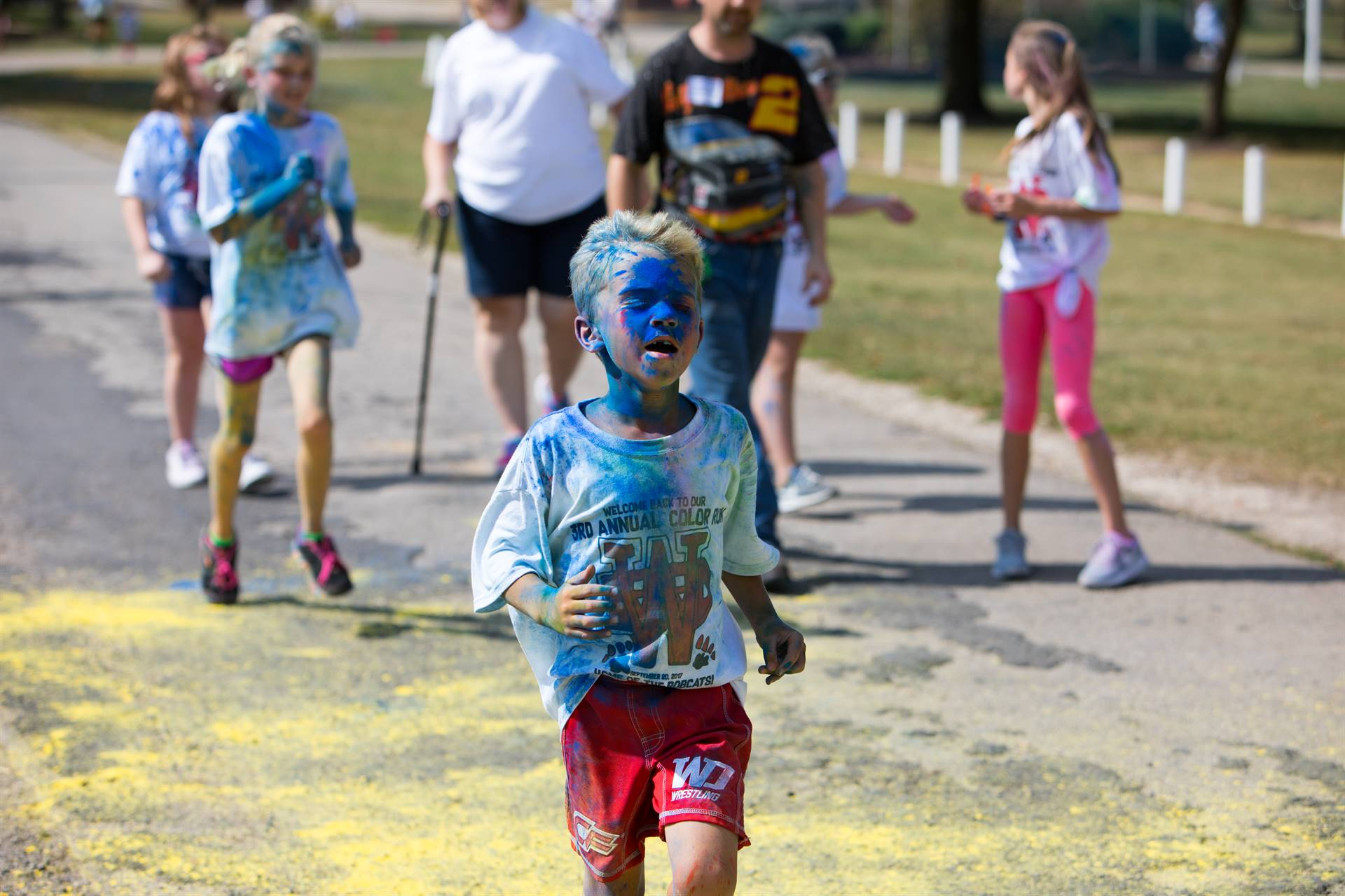 Boy with eyes closed at color run