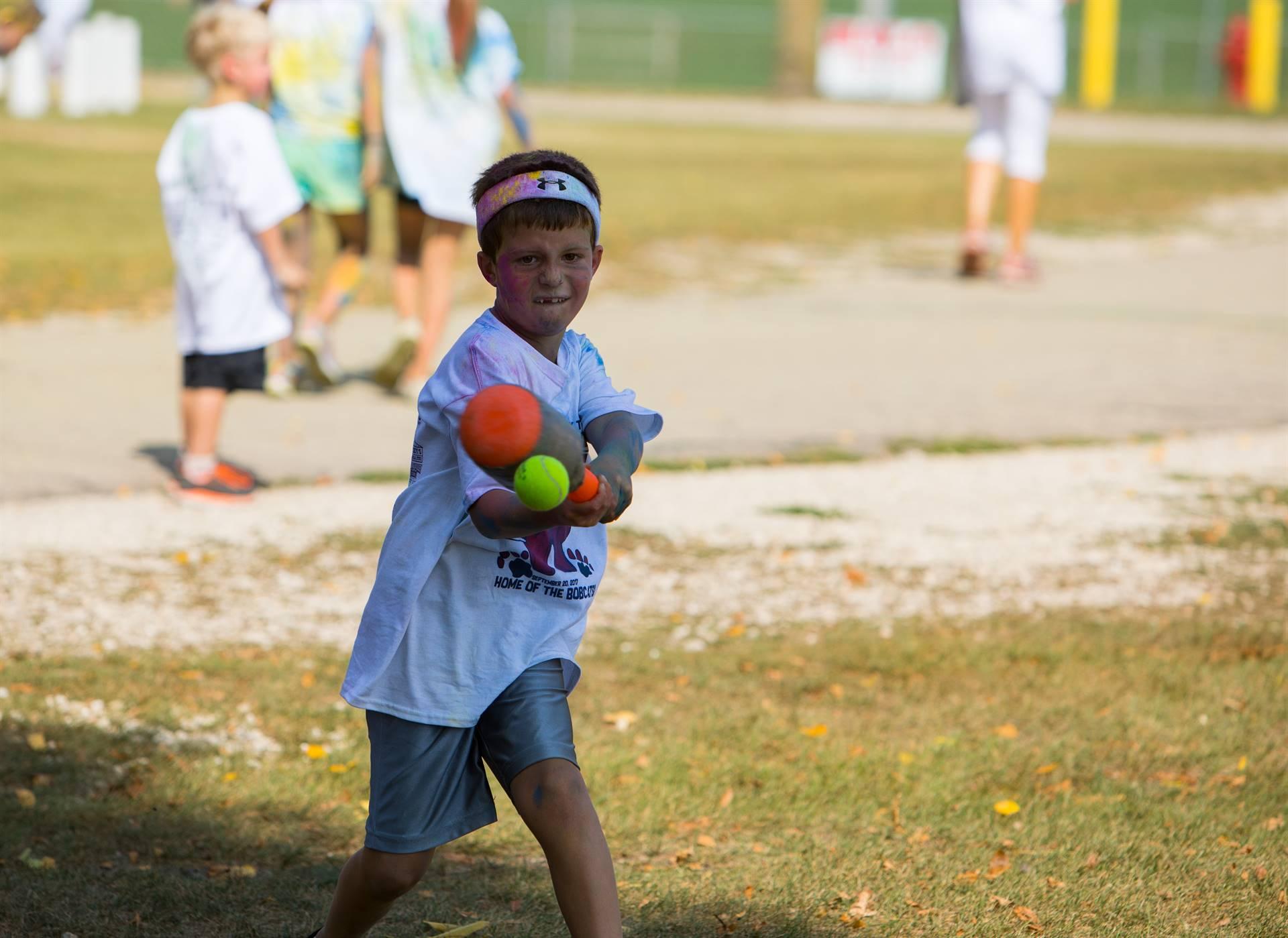 boy hitting ball with bat