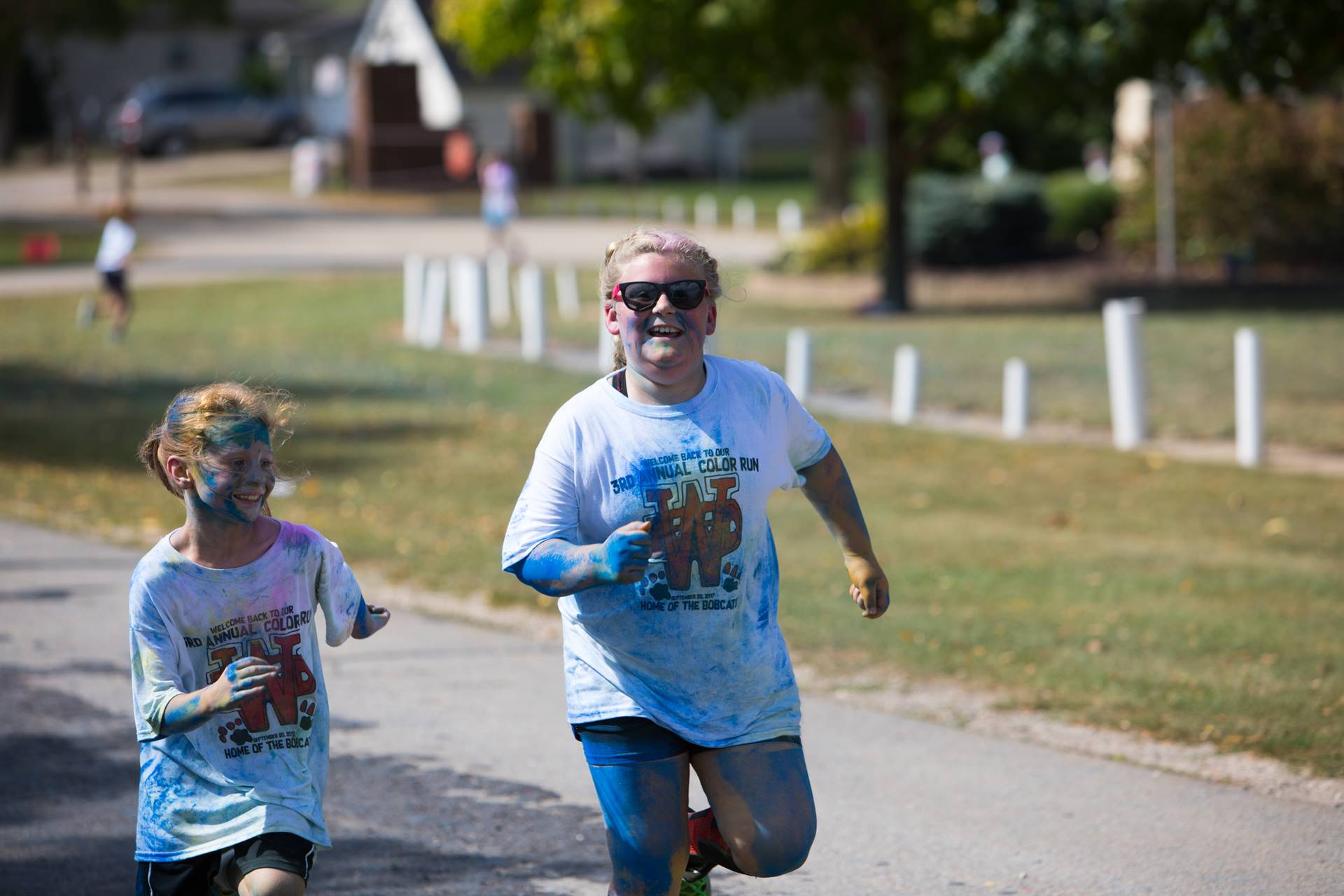 2 girls laughing and running at color run