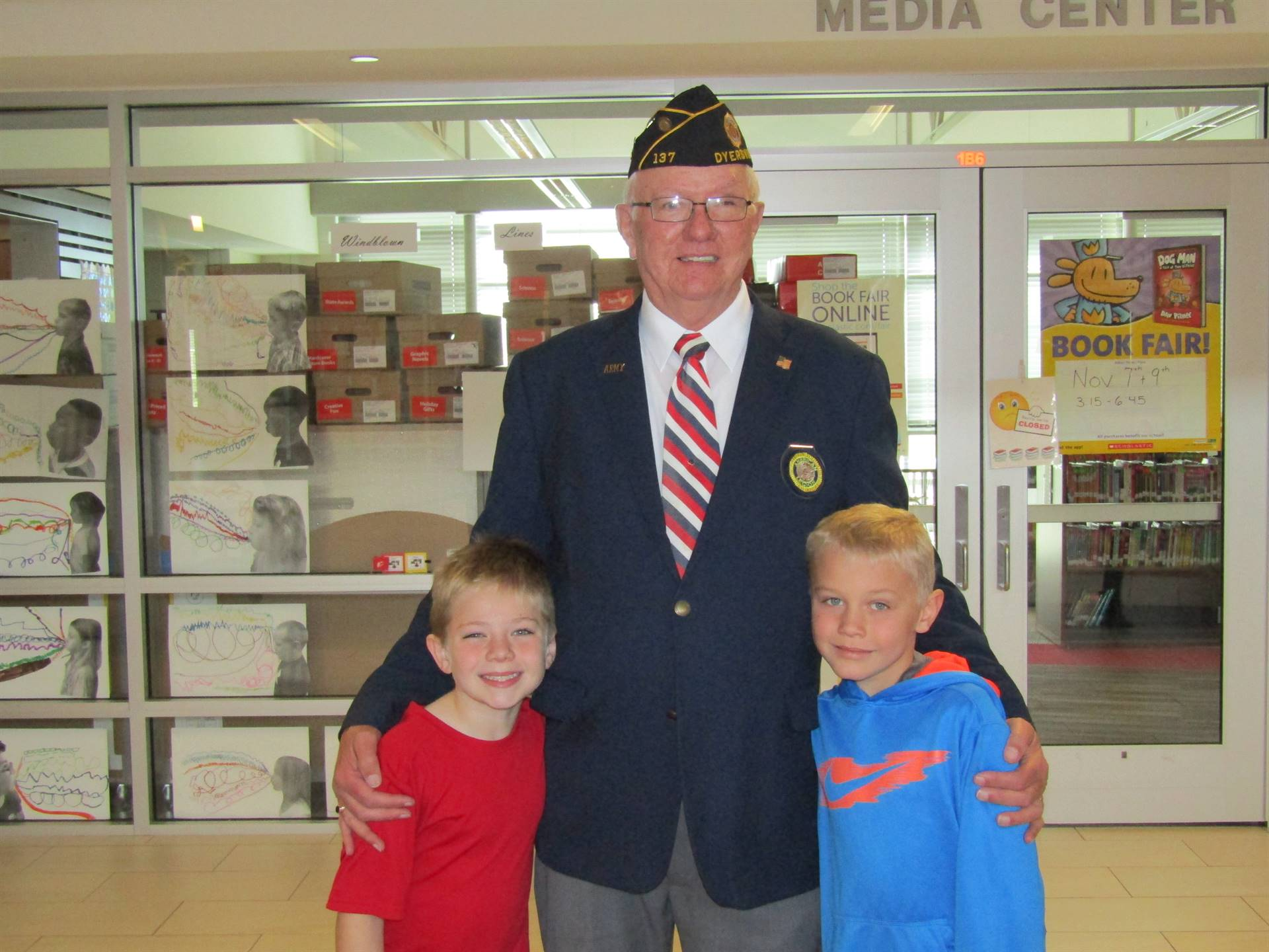 Dyersville Elementary 2nd and 3rd grade boy standing with Grandpa at Veterans Day assembly