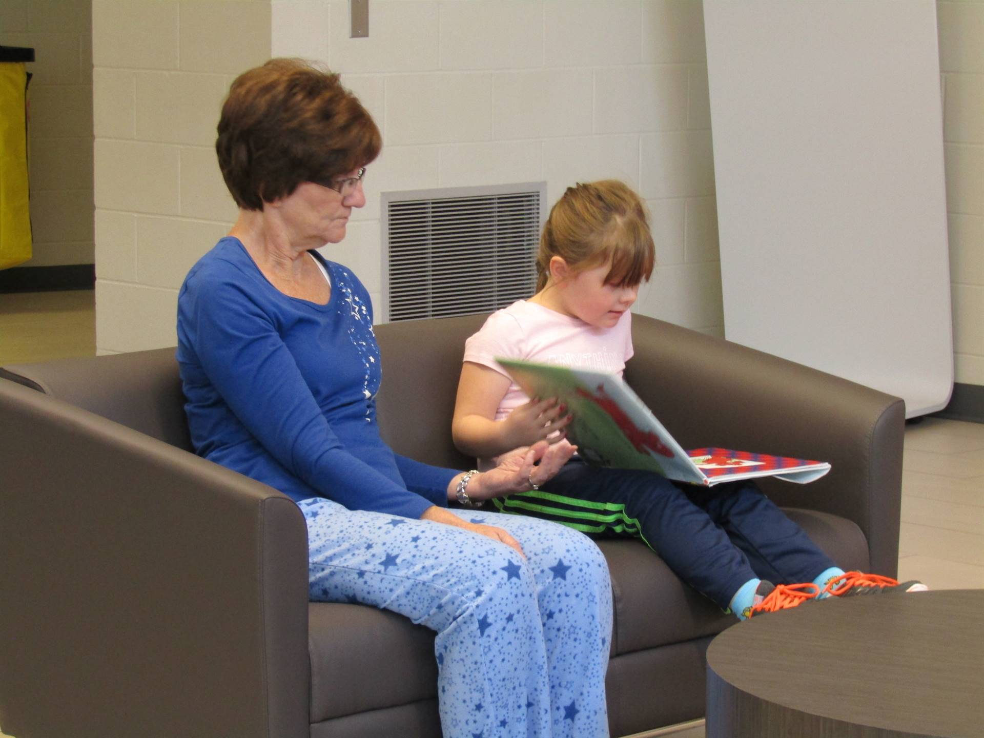 One of our paras reading with a student in our lobby.