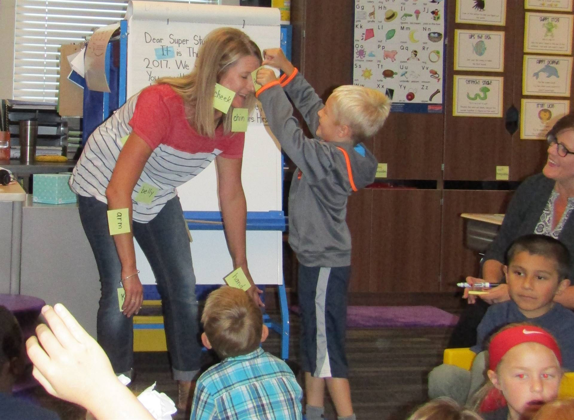 Elementary student putting a post it note on teacher during classroom labeling activity