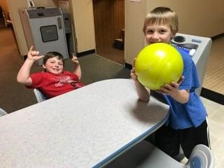 Two boys holding bowling ball