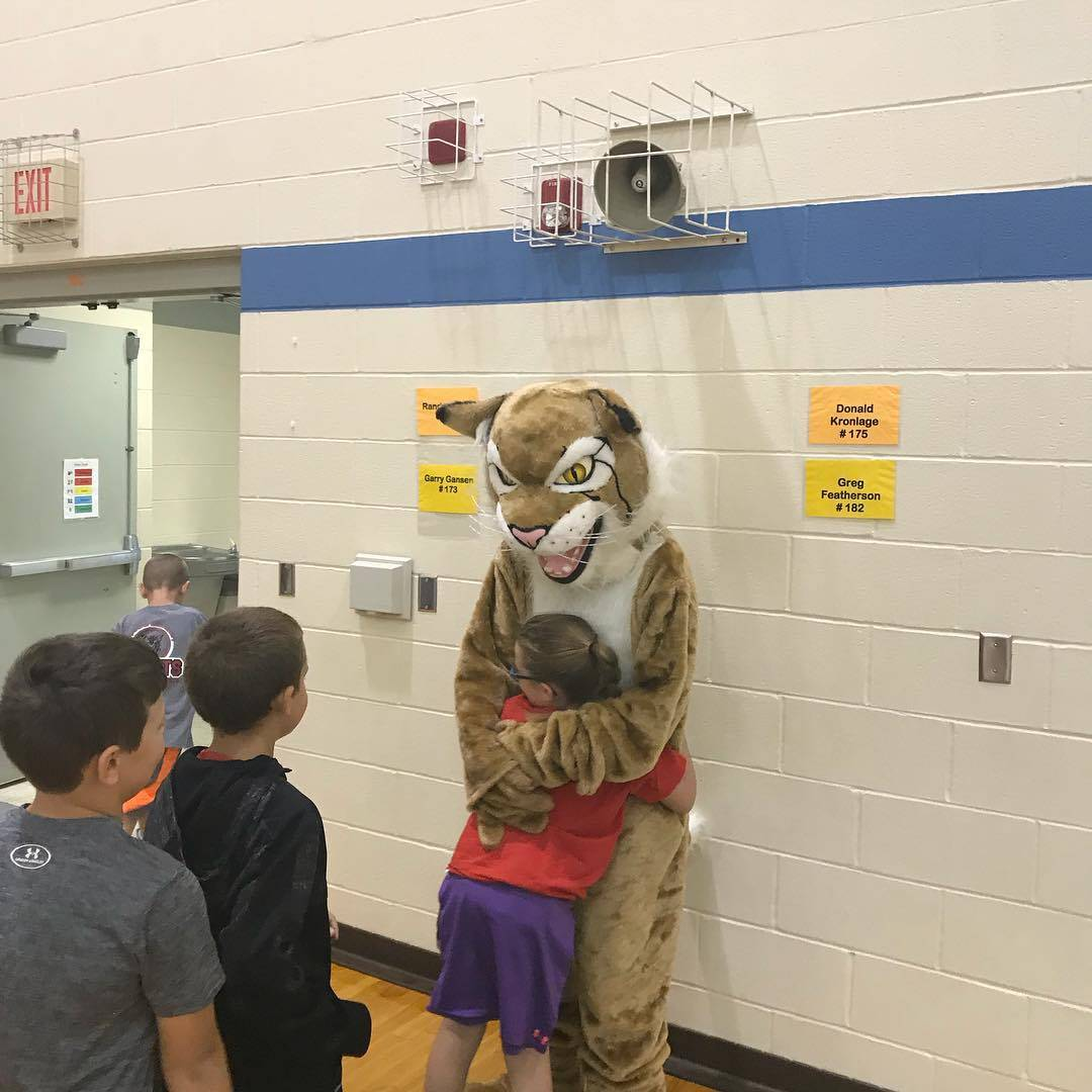 A second grader hugs Bruiser the Bobcat