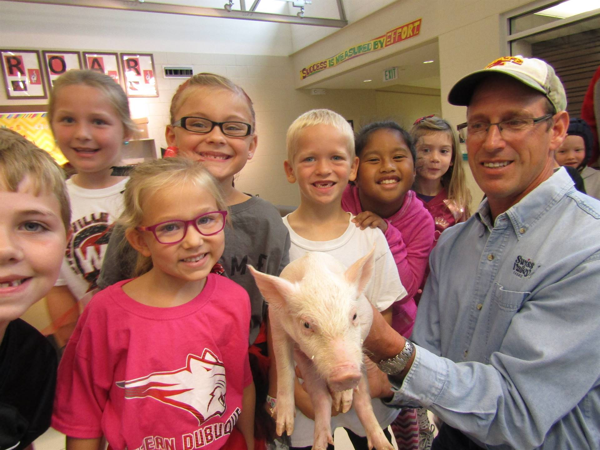 Pig farmer showing elementary students a pig