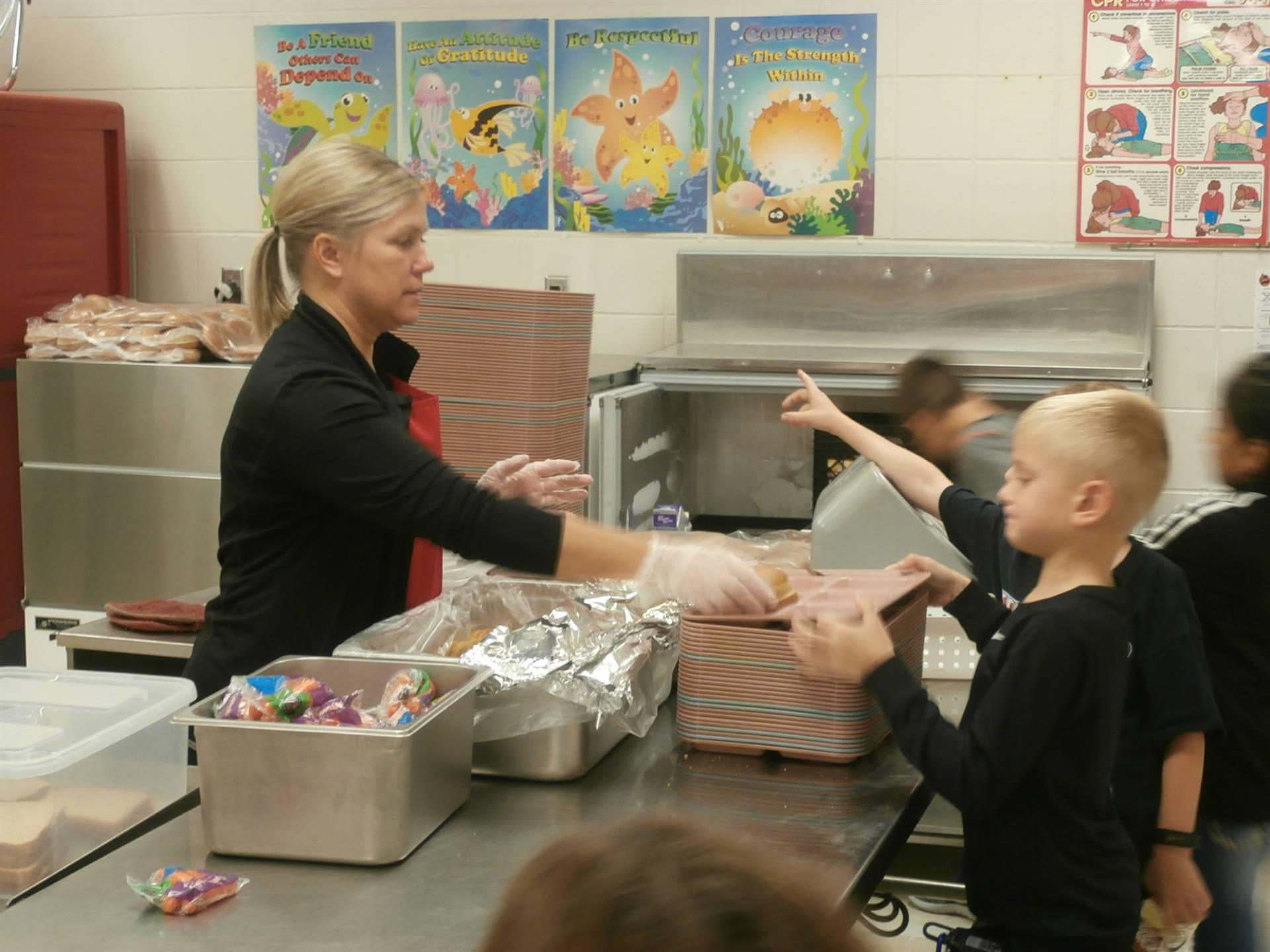 Food Service Worker serving lunch to students