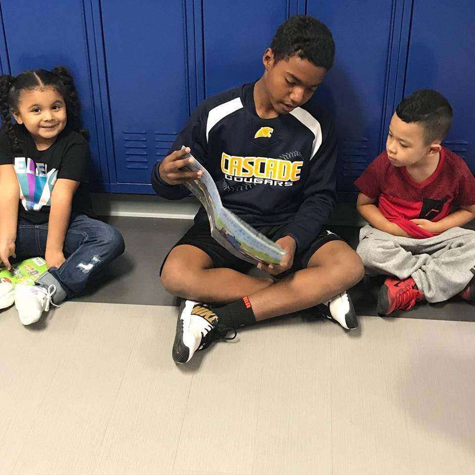 junior high student reading to elementary student