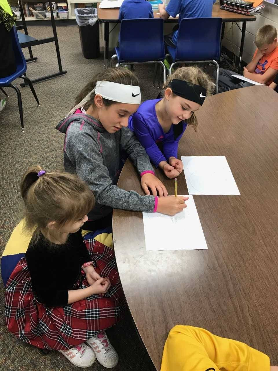 5th grade student helping two kindergarten students