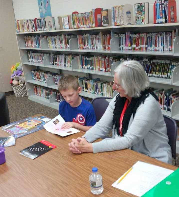 Foster Grandma Carol reading with 1st grade student