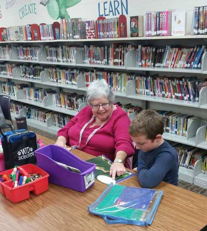Foster Grandma Lynn reading with 1st grade student