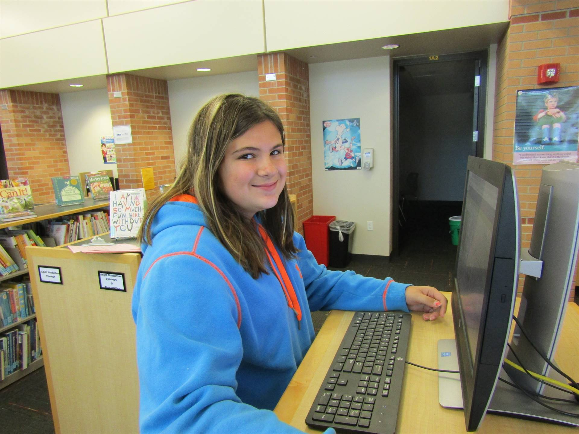 8th grade student uses the library computer to check out a book