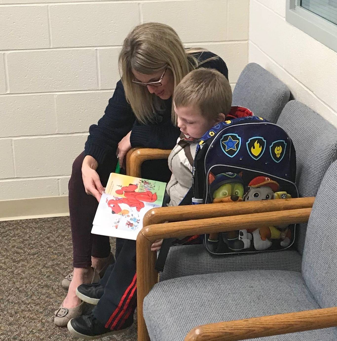 Secretary Kellie Kluesner reading with a young student