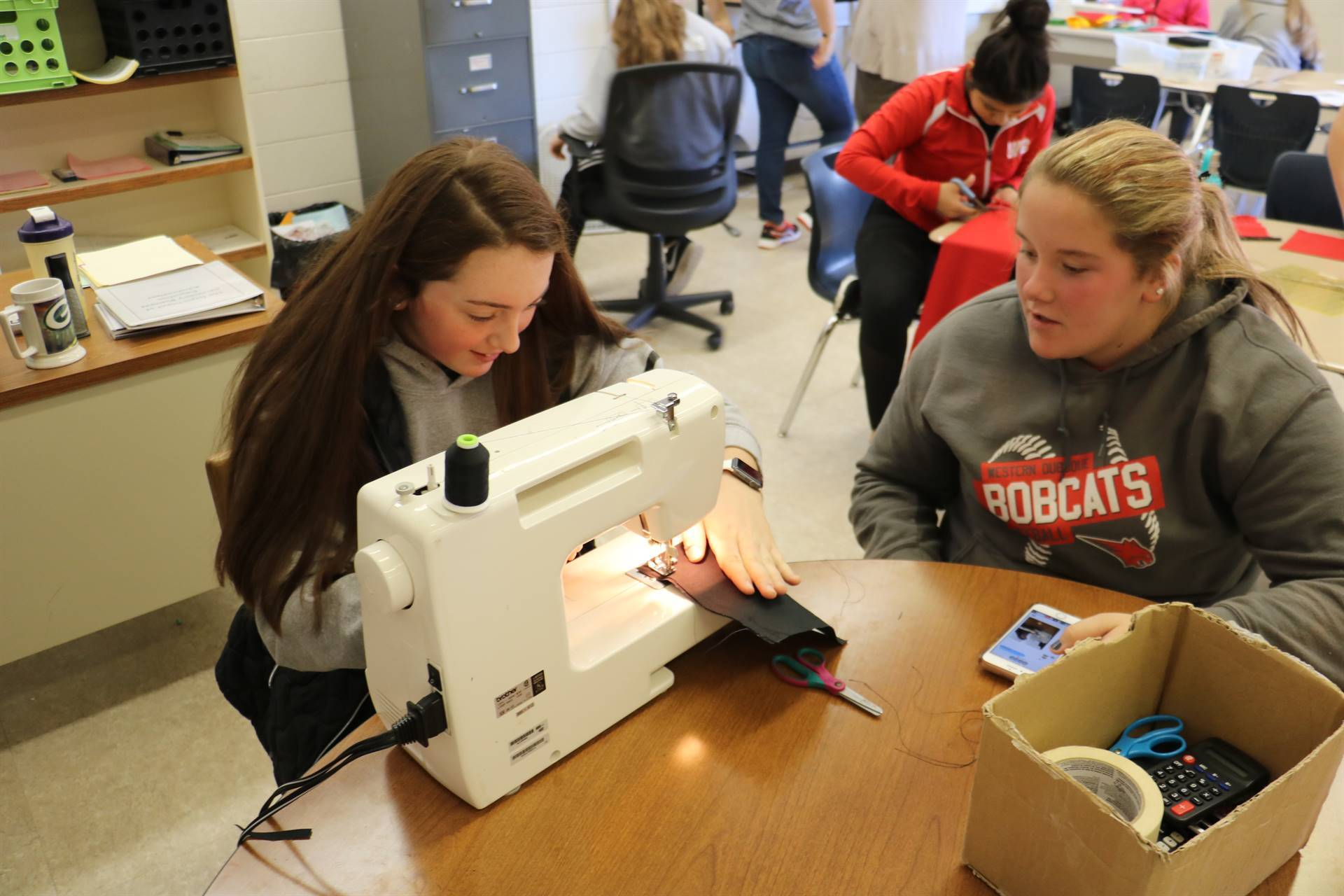 High school students working on sewing project