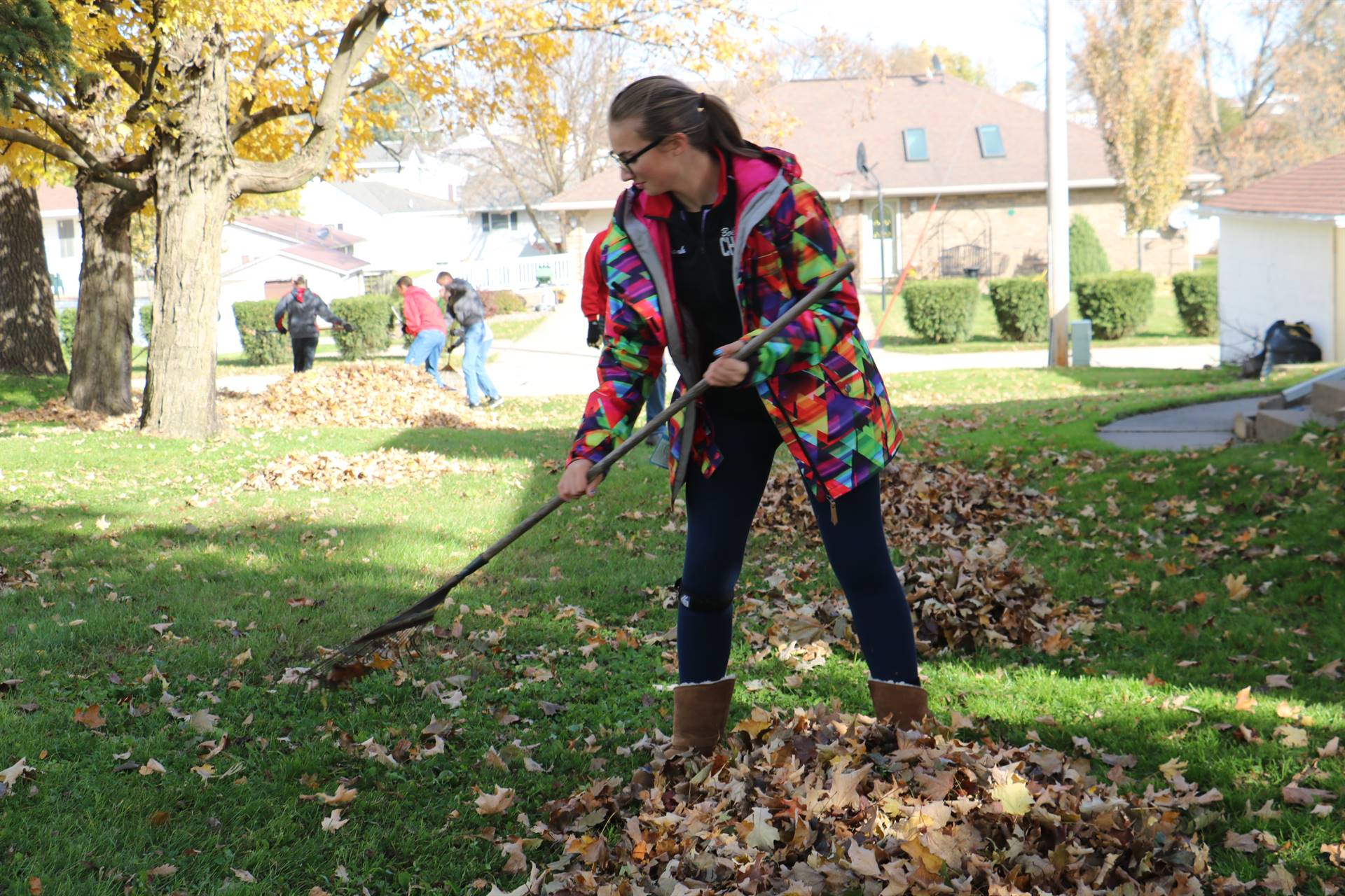 High school student raking leaves