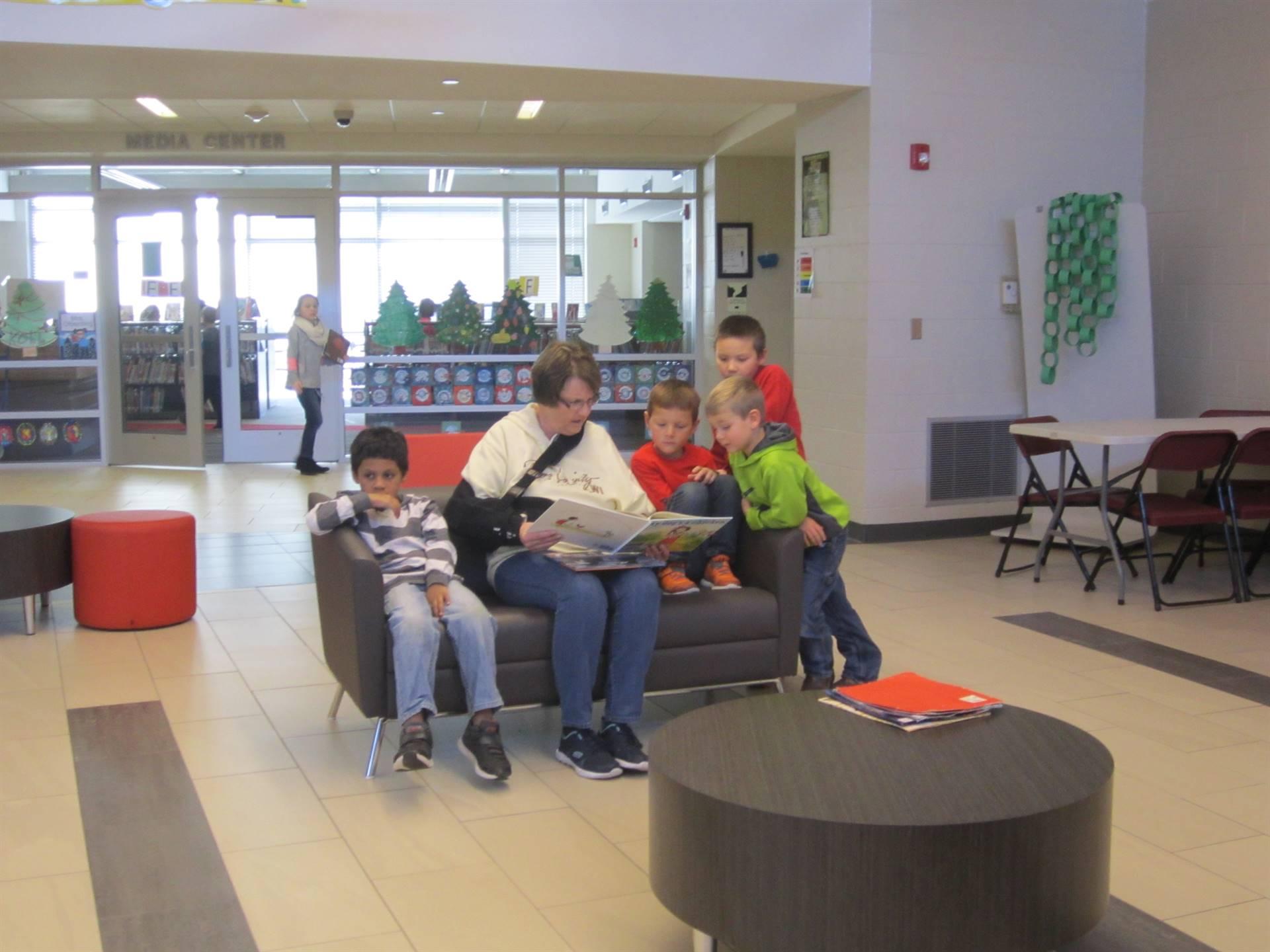 A volunteer reading with 4 kindergarteners