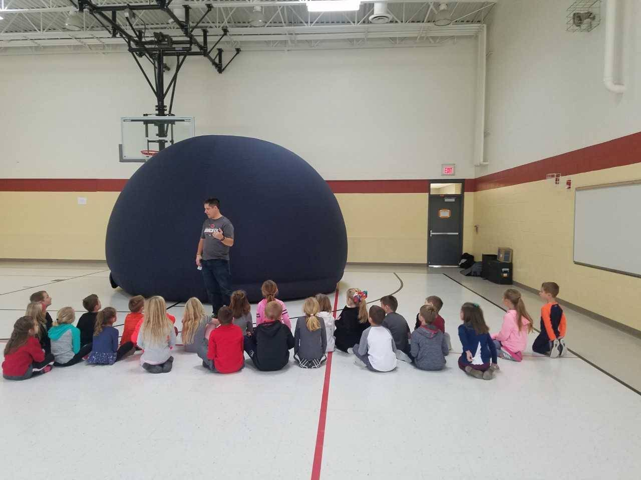 1st grade students sitting on floor while Mr. Palm talks to them about the planetarium