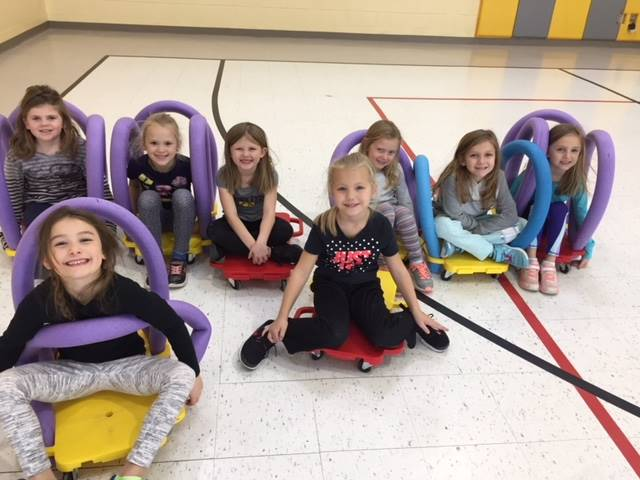 8 kindergarten girls sitting on scooters in gym class