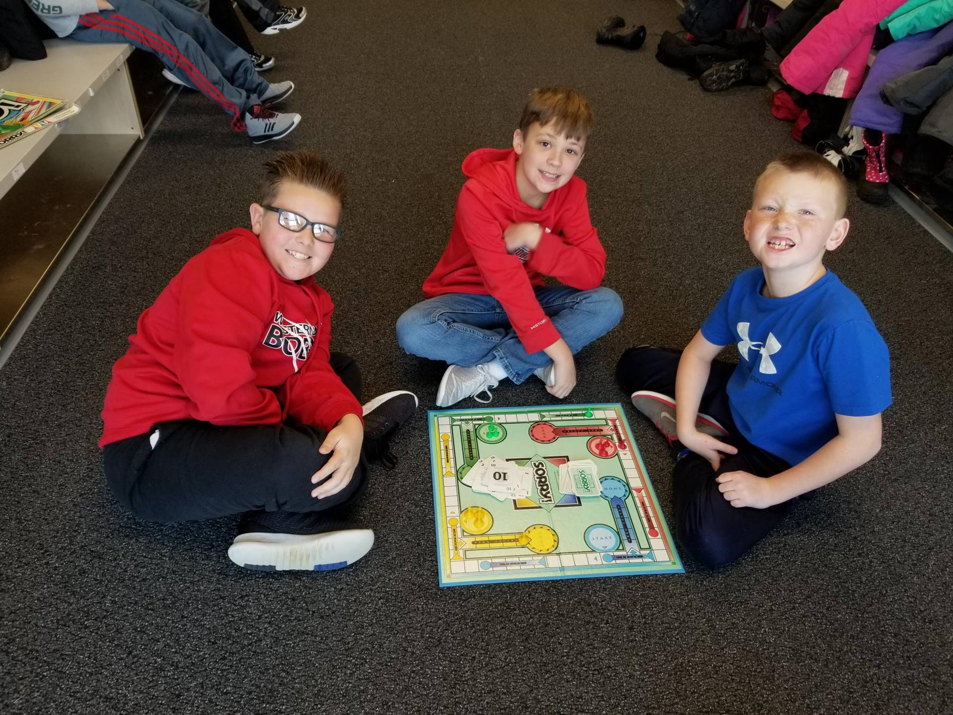 3 4th grade boys playing board game during indoor recess