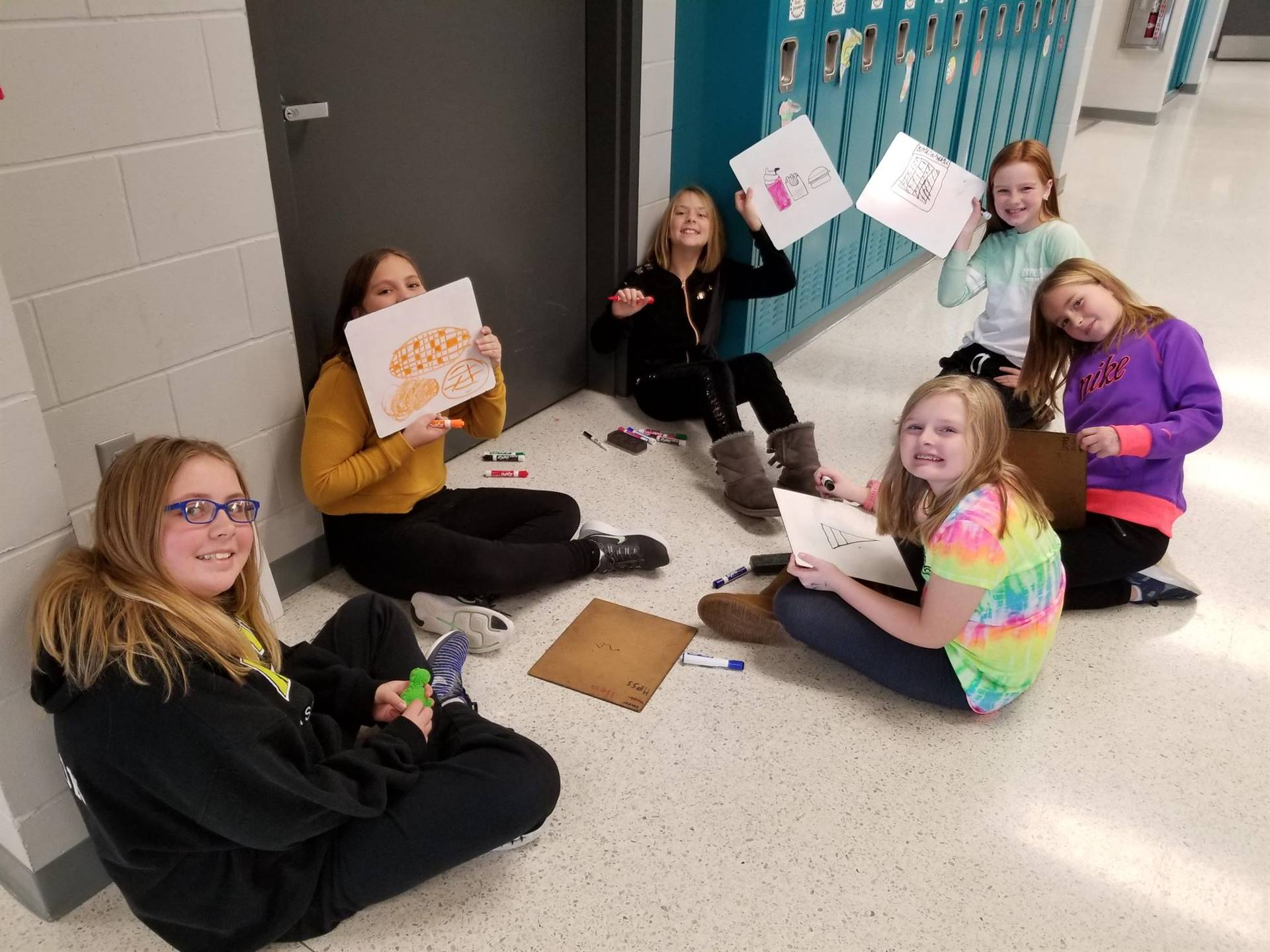 6 4th grade girls writing on white boards during indoor recess