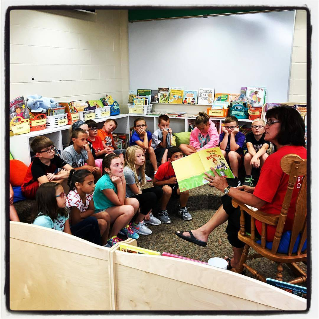 Mrs. Kramer is reading to 3rd grade students in the library