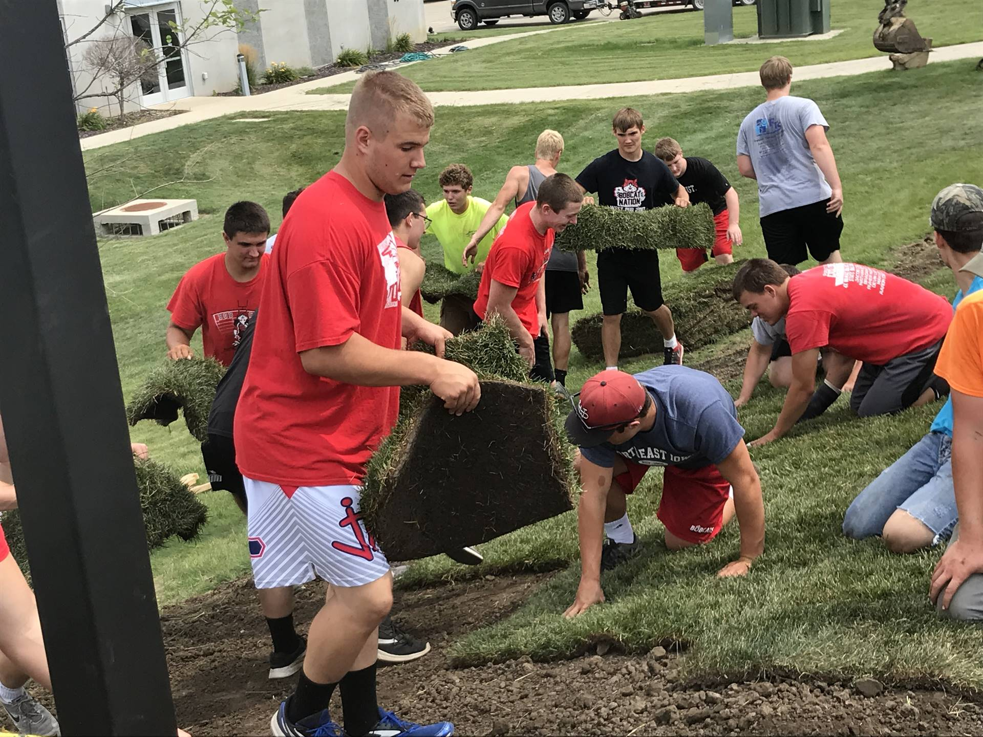 Football players working during Campus Cleanup