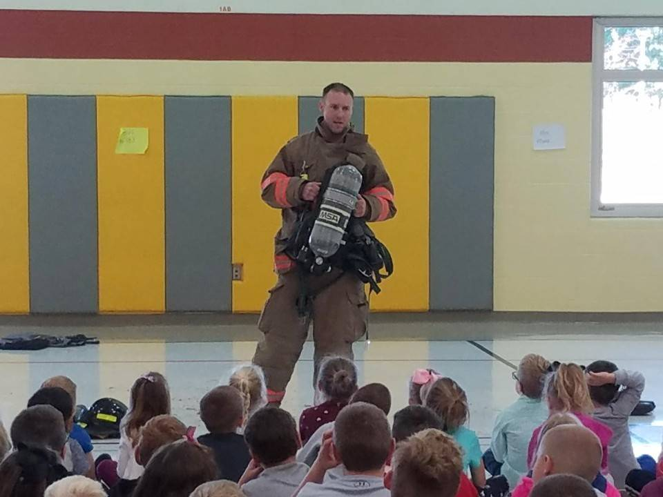 Firefighter speaking to students