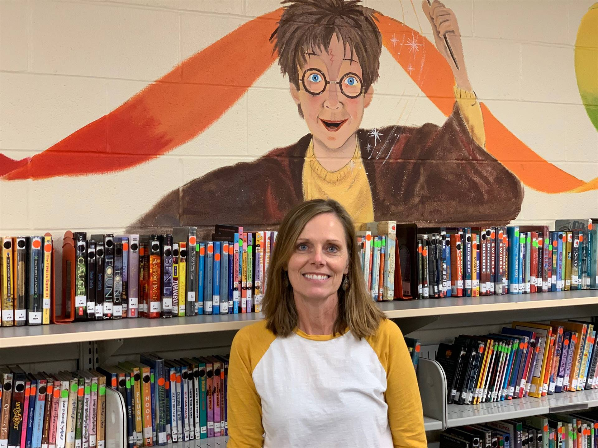 Beth Heim standing in front of her masterpiece in the library