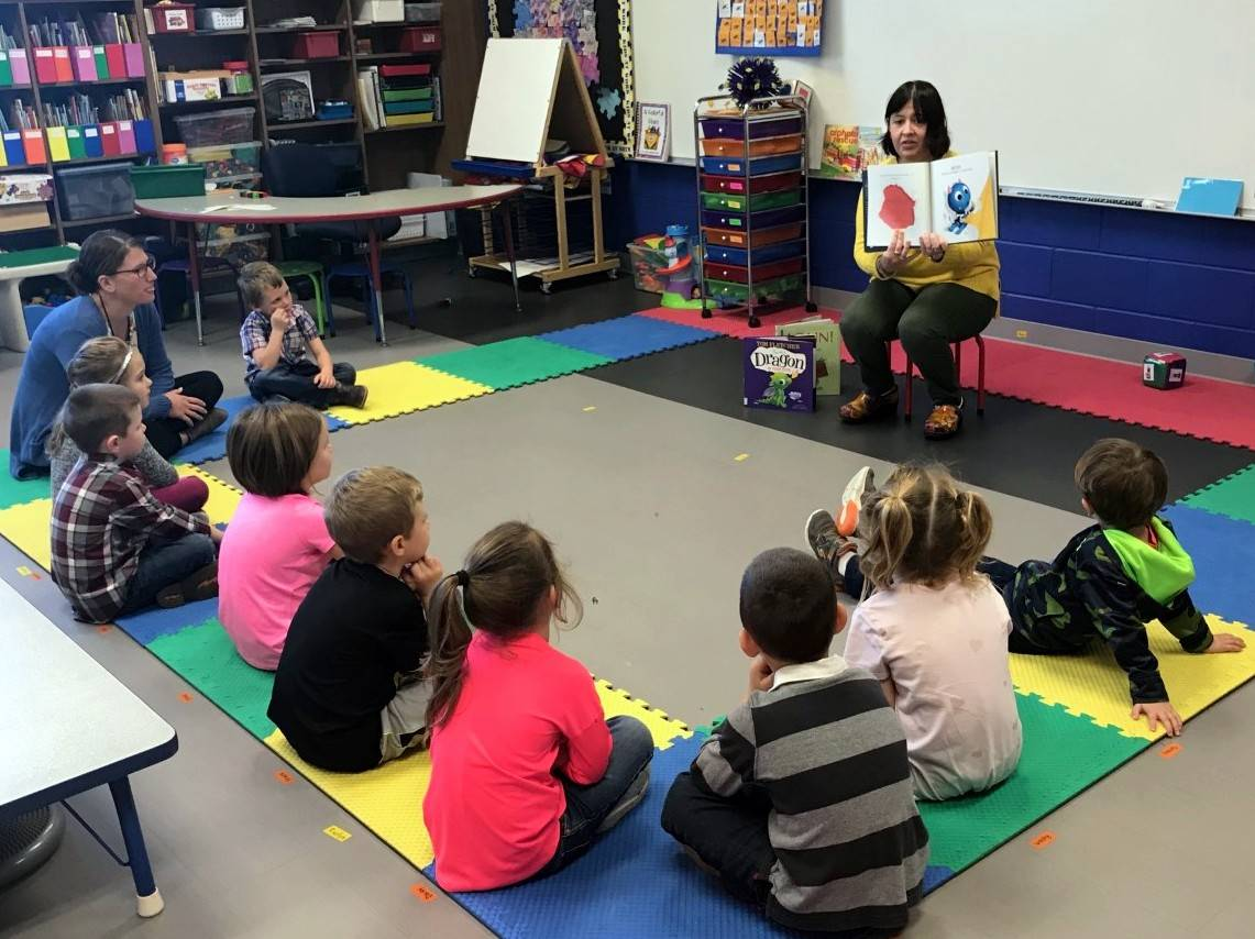 Business member reading to students
