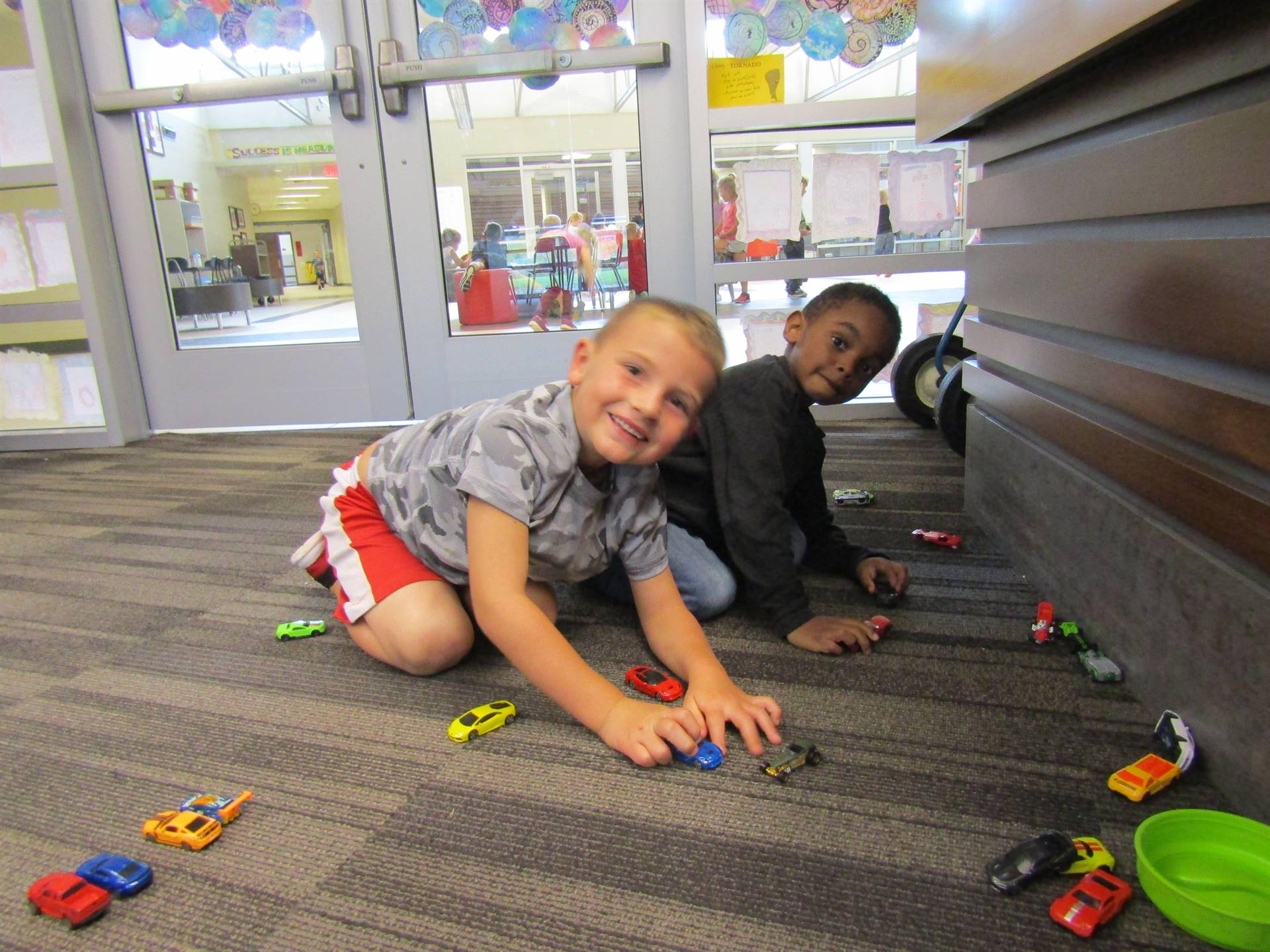 Boys playing with cars at indoor recess