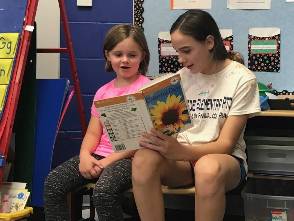Older student reading to younger student