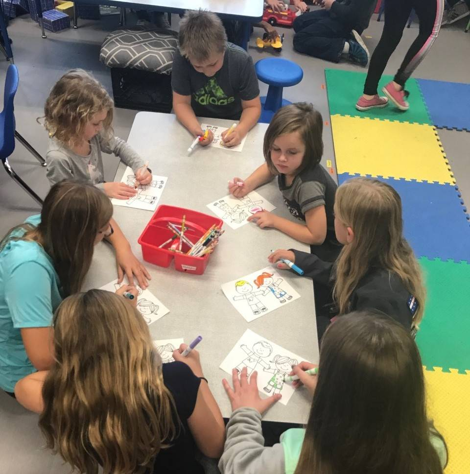 Older students coloring with younger students