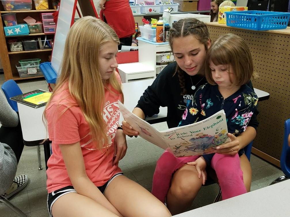 Older students reading to younger student