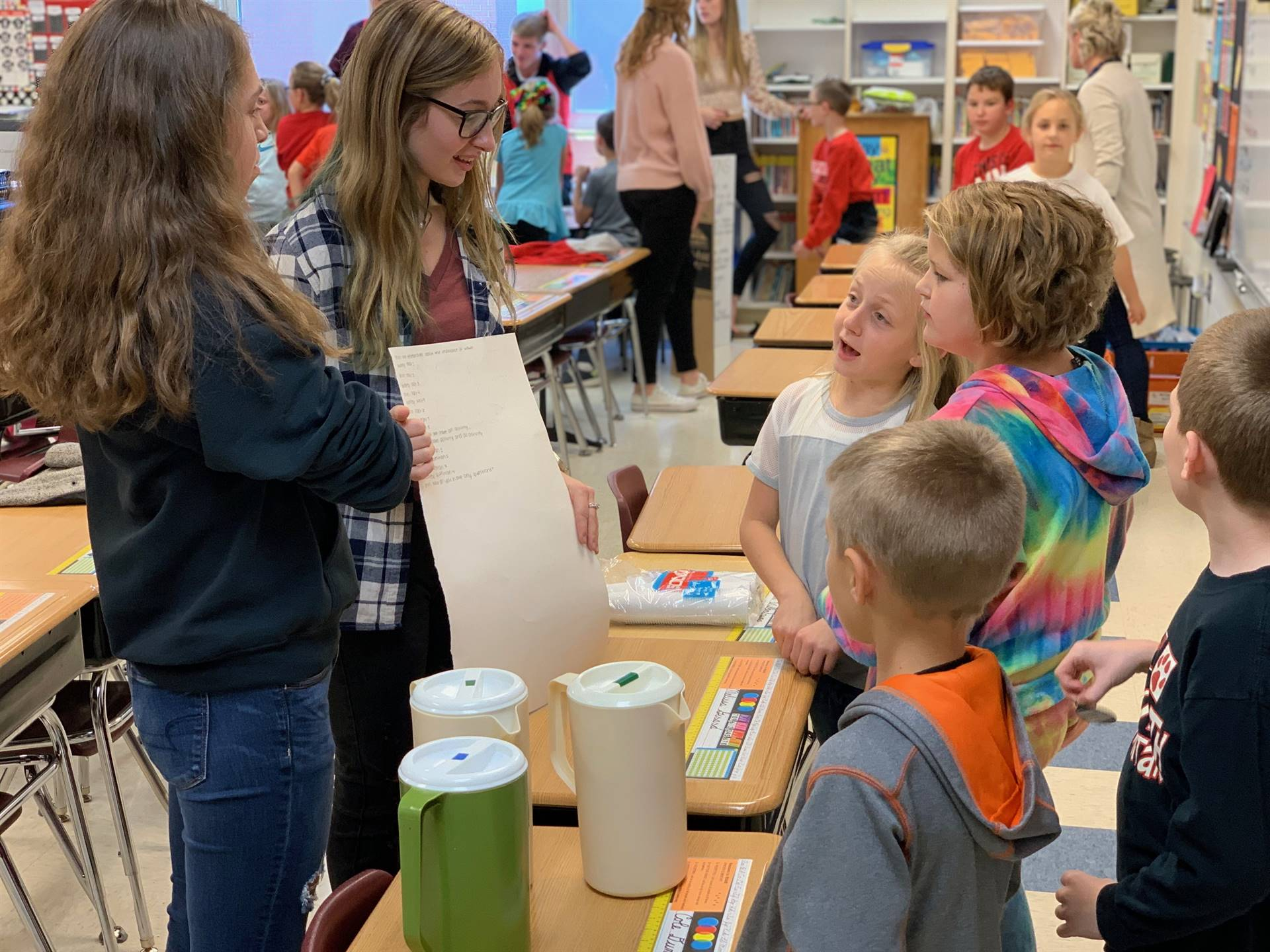 Elementary students working with high school student