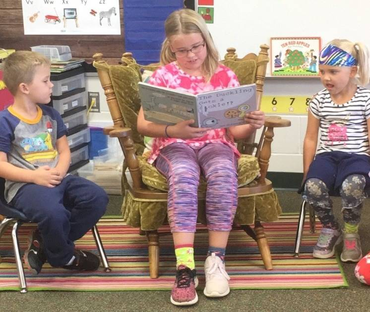 Older elementary student reading to younger students