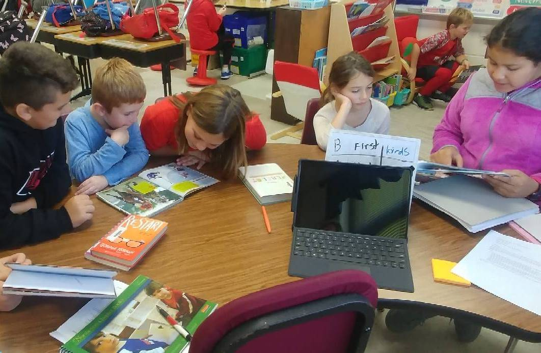 Older elementary students working with younger students