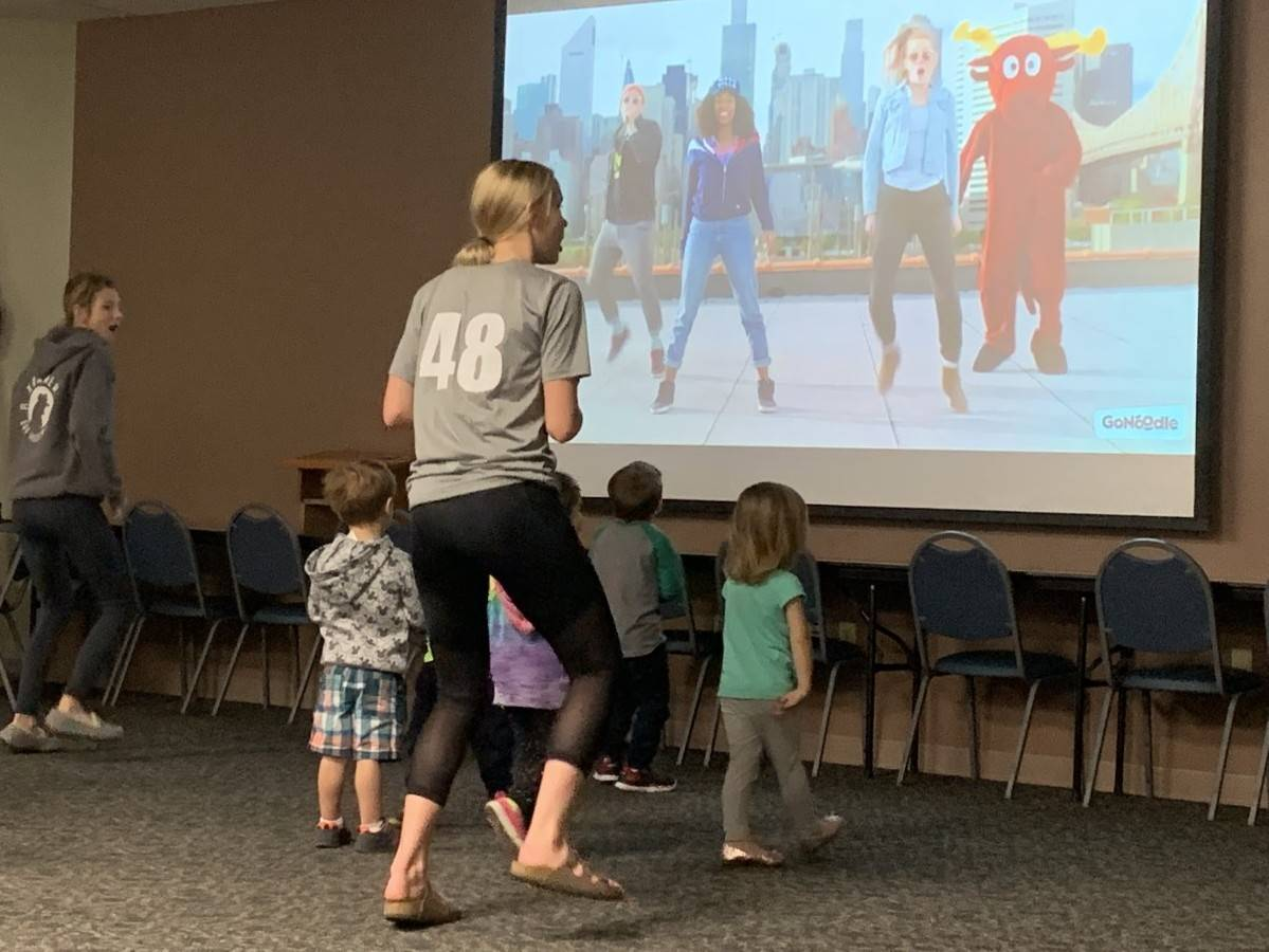 HIgh school students teaching dance steps to younger students