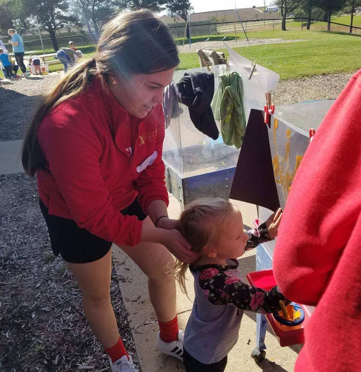 High school student helping younger child with art project