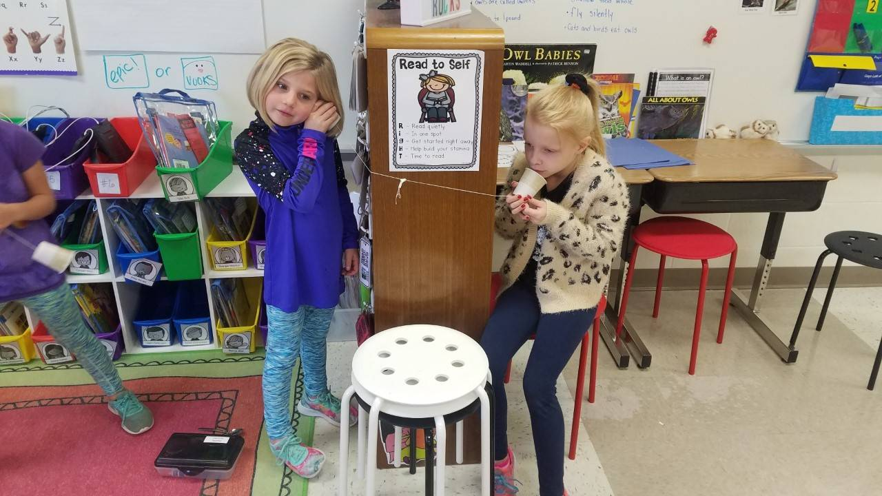 Two 1st Grade Girls Playing Telephone