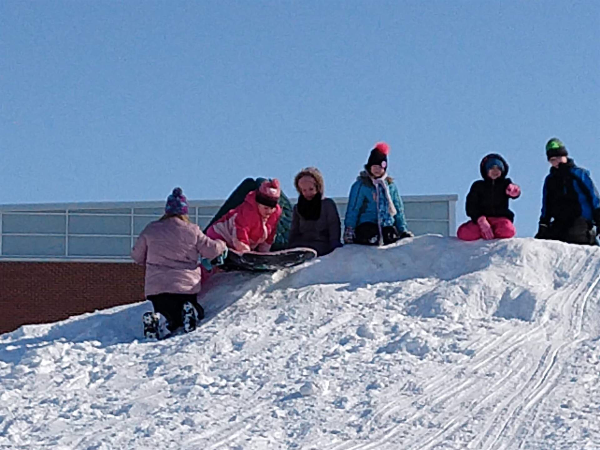Students have fun on the snowy hillside at recess.