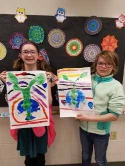 5th graders proudly display their Earth Day posters