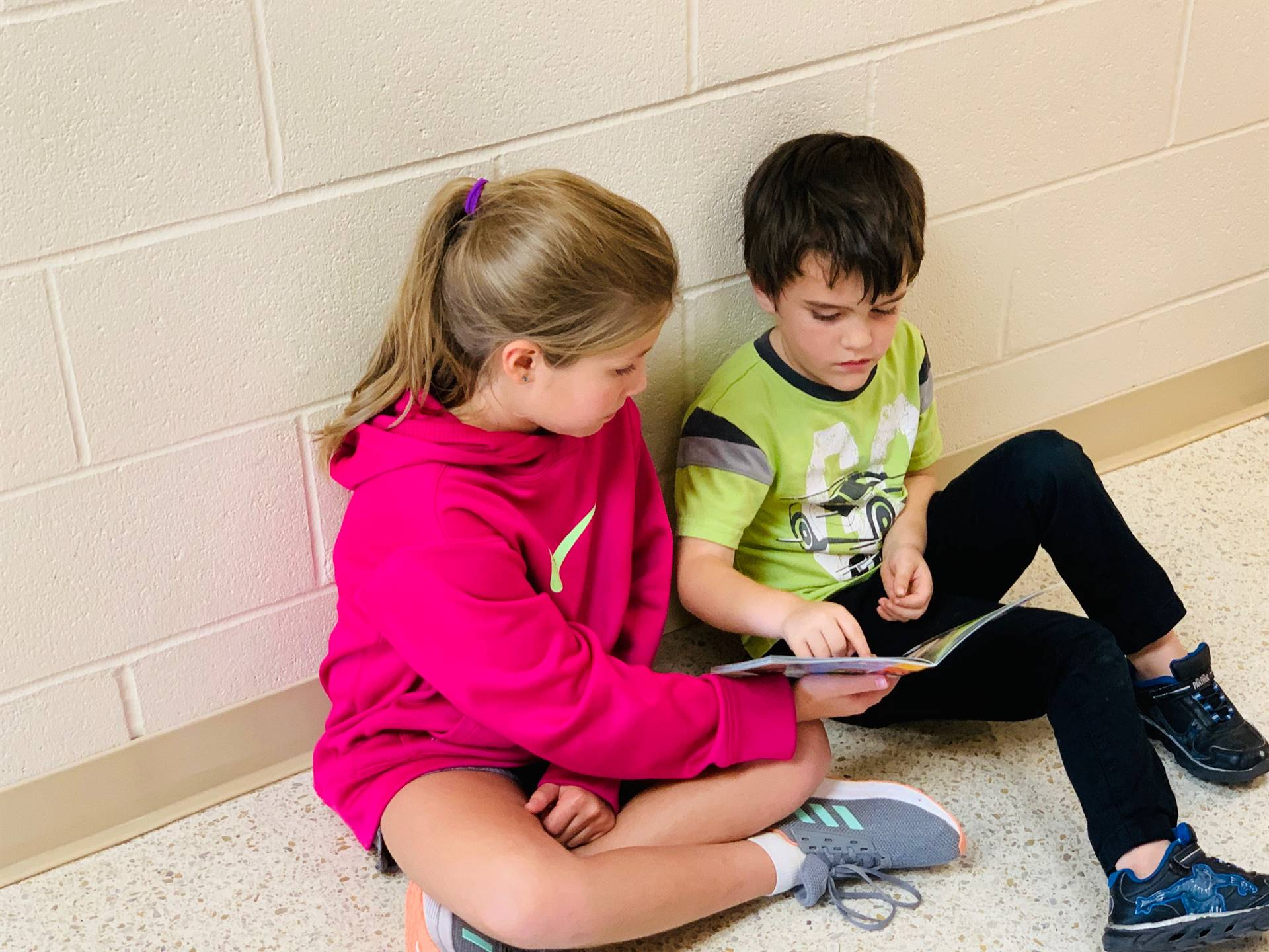 A fourth grader assists a kindergarten student with letter tracing