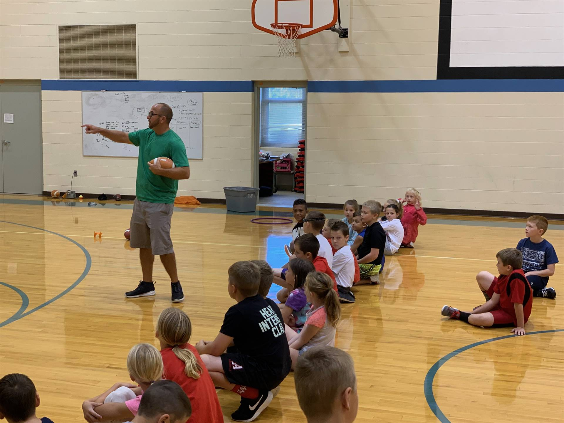 Mr. Ball provides instruction to fourth graders on the basics of kicking in football