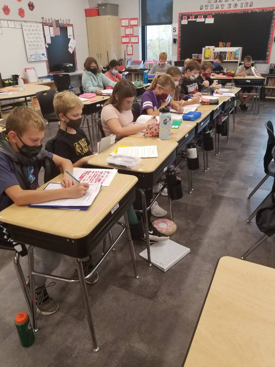 5th grade students writing in science notebooks at desks