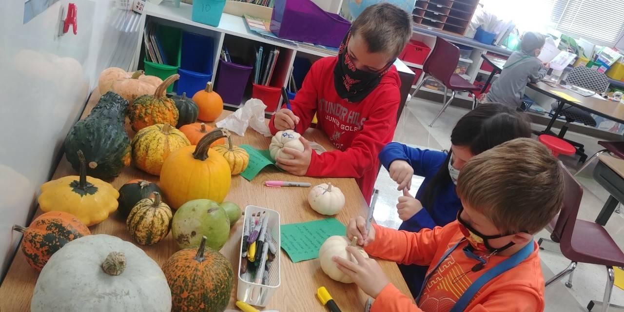 First grade students coloring pumpkins