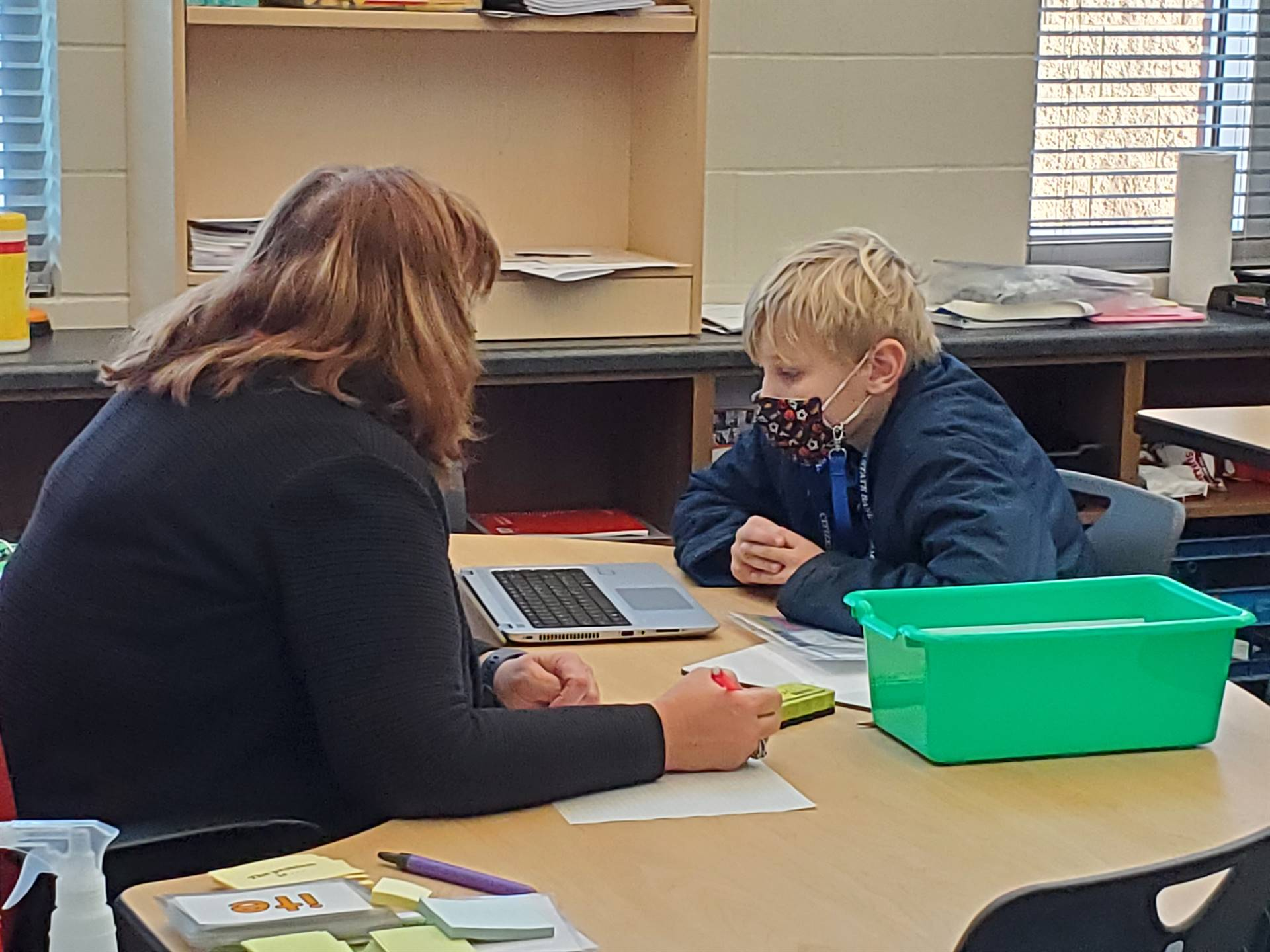 Teacher working with a student on reading