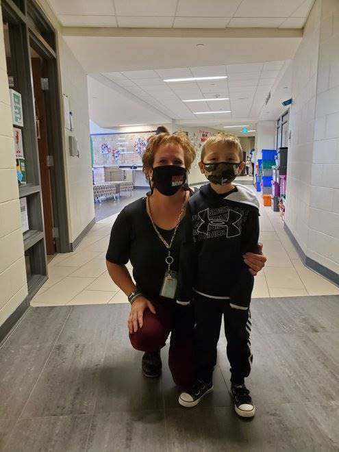 A paraprofessional and her student in the hallway