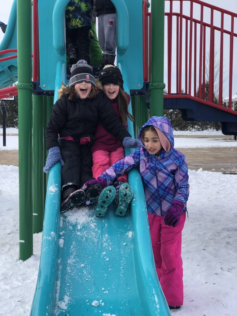 3-4th grade girls playing on slide at recess